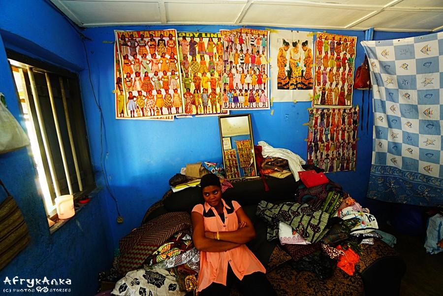 Wnętrze salonu z wzorami sukienek na ścianie.