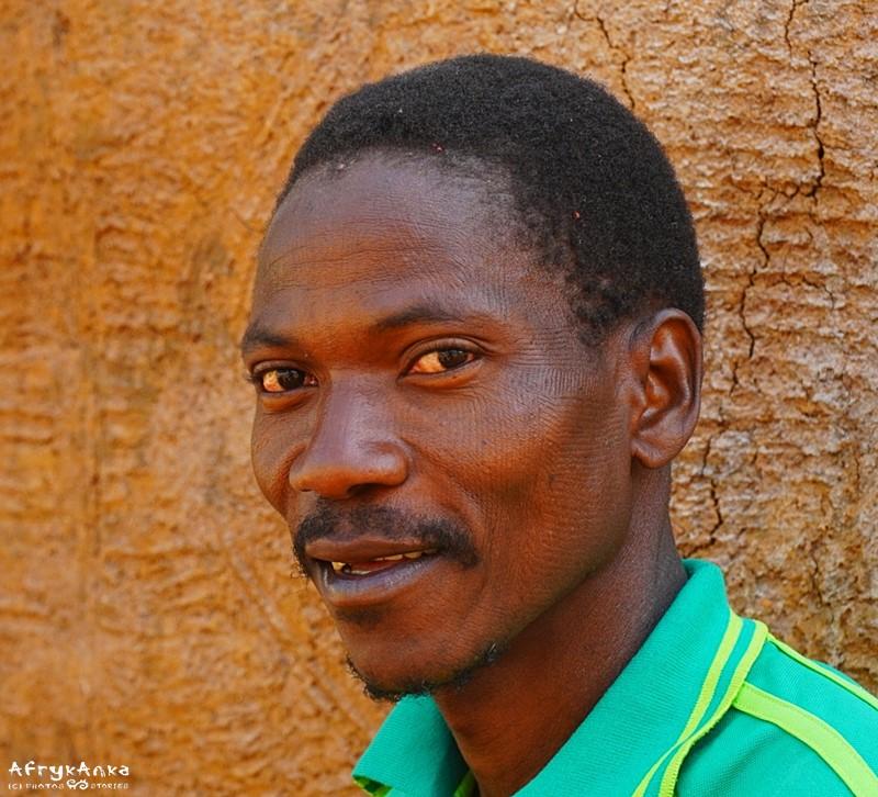 Matjas - szef wioski - na tle swego domu.