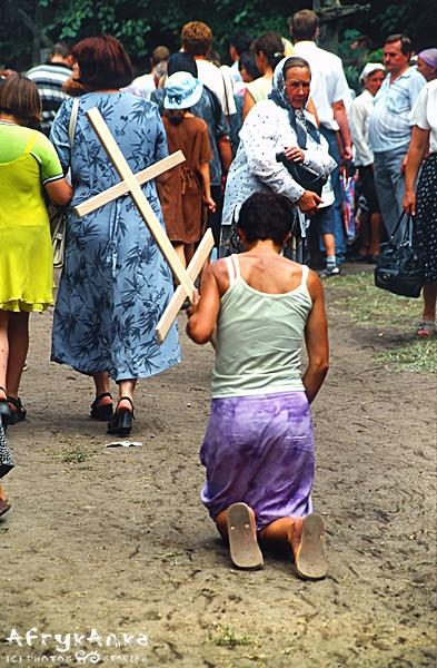 Niektórzy pątnicy na kolanach obchodzą cerkiew.